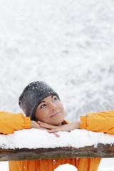 Junge Frau im Schnee, stützte sich auf Holzgeländer