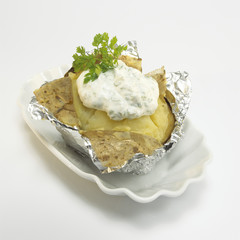 Ofenkartoffel mit Sauerrahm in Folie, close-up