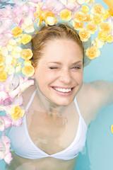 Deutschland, junge Frau im Pool, Nahaufnahme mit Blüten