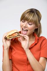 Frau jung, mit Hamburger, mit offenem Mund, close-up