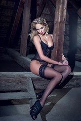 Sensual woman in underwear sit on timber