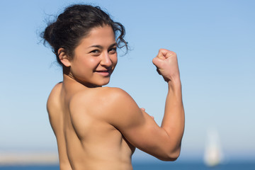 Topless athlete demonstrates muscles