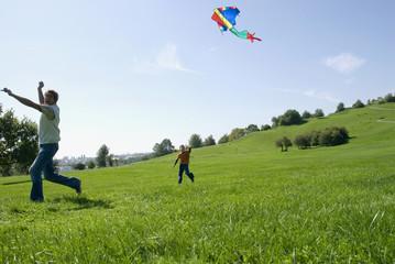 Vater und Sohn Drachen steigen im Park