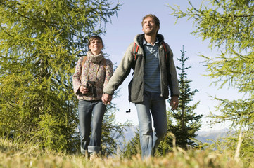 Junges Paar läuft über Wiese, Händchen haltend