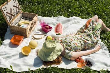 Junge Frau liegt auf Picknickdecke