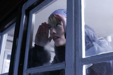 Frau schaut durch Fenster