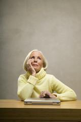 Seniorin sitzt mit der Hand am Kinn vor Laptop auf dem Tisch, close-up