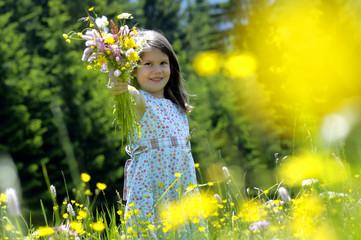 Mädchen mit Blumenstrauß in der Wiese, lächeln