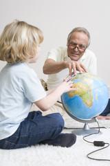 Großvater und Enkel (8-9), mit Globus