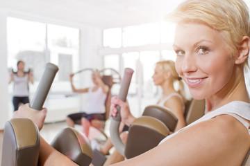Deutschland, Frauen im Fitnessstudio, lächelnd