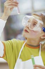 Mädchen mit Schutzbrille und Reagenzglas