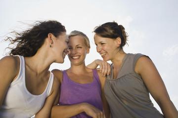 Deutschland, Bayern, Drei junge Frauen nebeneinander, lachen
