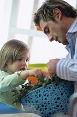 Vater und Sohn prüfen frische Kräuter in der Küche