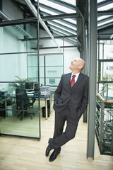 Deutschland, München, Geschäftsmann stehen Büro, die Hände in den Taschen