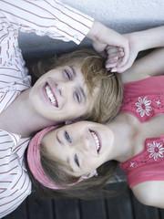 Junges Paar auf dem Boden liegend, Hände haltend