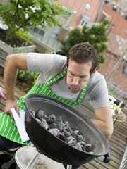 Mann vorbereiten Grillen auf dem Balkon
