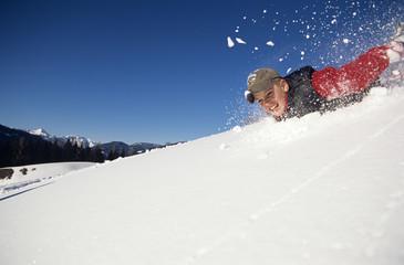 Junge rutscht auf Schnee-Piste