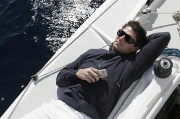 Mann liegt auf dem Segelboot mit Handy