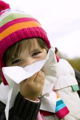 Kleines Mädchen putzt sich die Nase, Erkältung