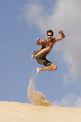 Mann springt auf Sanddüne in die Luft