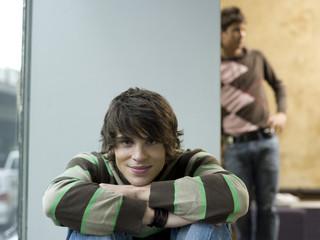 Junger Mann hockend, anderer junger Mann im Hintergrund