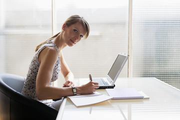 Frau am Schreibtisch Schreiben im Notizblock