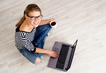 Young smiling female searching internet for home design