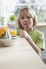 Junge (8-9) hält Glas mit frisch gepresstem Orangensaft, Porträt