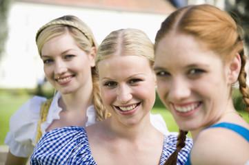 Deutschland, Bayern, Oberbayern, Drei Frauen in traditionellen Kostümen, Lächeln, Portrait