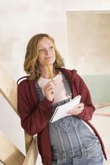 Junge Frau mit Bleistift, macht sich Notizen