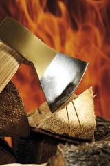 Axt und Brennholz, Feuer im Hintergrund