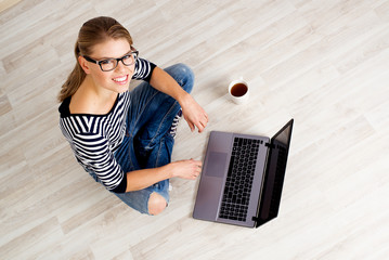 Pretty smiling woman working on-line at computer