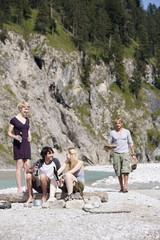 Deutschland, Bayern, Tölzer Land, junge Leute sitzen auf Baumstamm in der Nähe Flusses