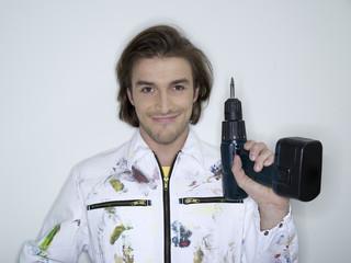 Mann hält Bohrmaschine, Portrait
