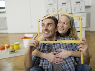 Junges Paar mit Zollstock in Form eines Hauses, Portrait