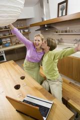 Paar in der Küche mit Laptop, Jubel, Portrait