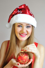 Attractive young woman holding red Christmas ball