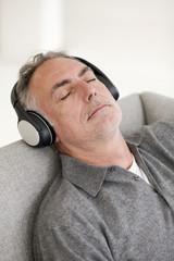Reifer Mann mit Kopfhörern, die Augen geschlossen, close-up