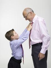 Enkel (8-9) bindet dem Großvater die Krawatte, Portrait