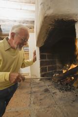 Älterer Mann schürt Feuer im Kamin