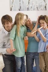Familie im Wohnzimmer, Sohn (7-9) spielt Blockflöte