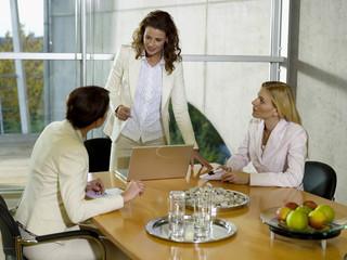 Geschäftsfrauen in Besprechung, am Schreibtisch mit Laptop
