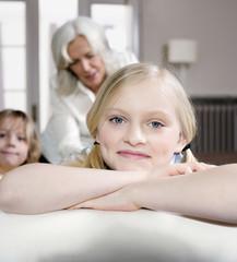 Mädchen (8-9) Lächelt, portrait, Bruder (8-9) und Großmutter im Hintergrund