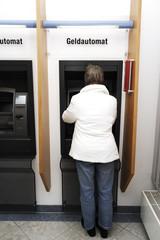 Frau am Geldautomat, Rückenansicht