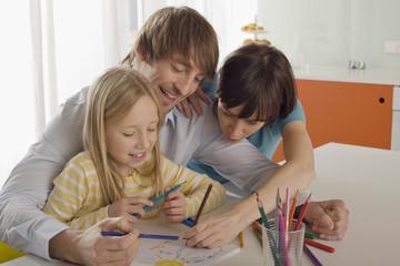 Mädchen (8-9) malt mit den Eltern