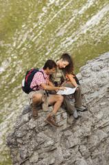 Österreich, Salzburger Land, Paar sitzt auf Felsen