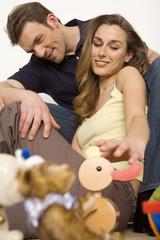 Junges Paar schaut auf Spielzeug auf dem Boden