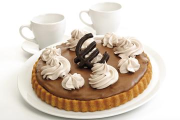 Schokoladenbiskuit mit Eurozeichen und zwei Tassen Kaffee