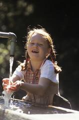 Mädchen spielt am Brunnen, lächelnd