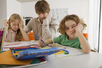 Vater und Kinder machen Hausaufgaben